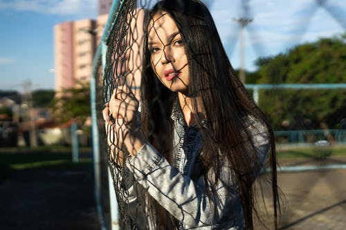Woman leaning forward on a chain-link fence