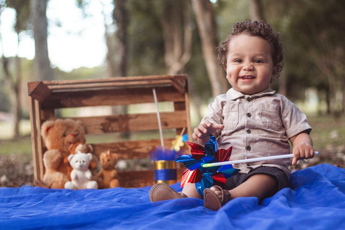 Photo of a baby boy Siting on Blue fabric holding a toy