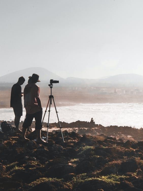 Two Men Standing on Rock Taking Photo Body of Water