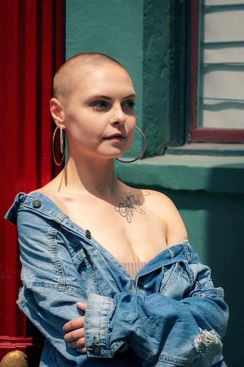 Photo of a woman wearing a blue denim jacket standing near a window