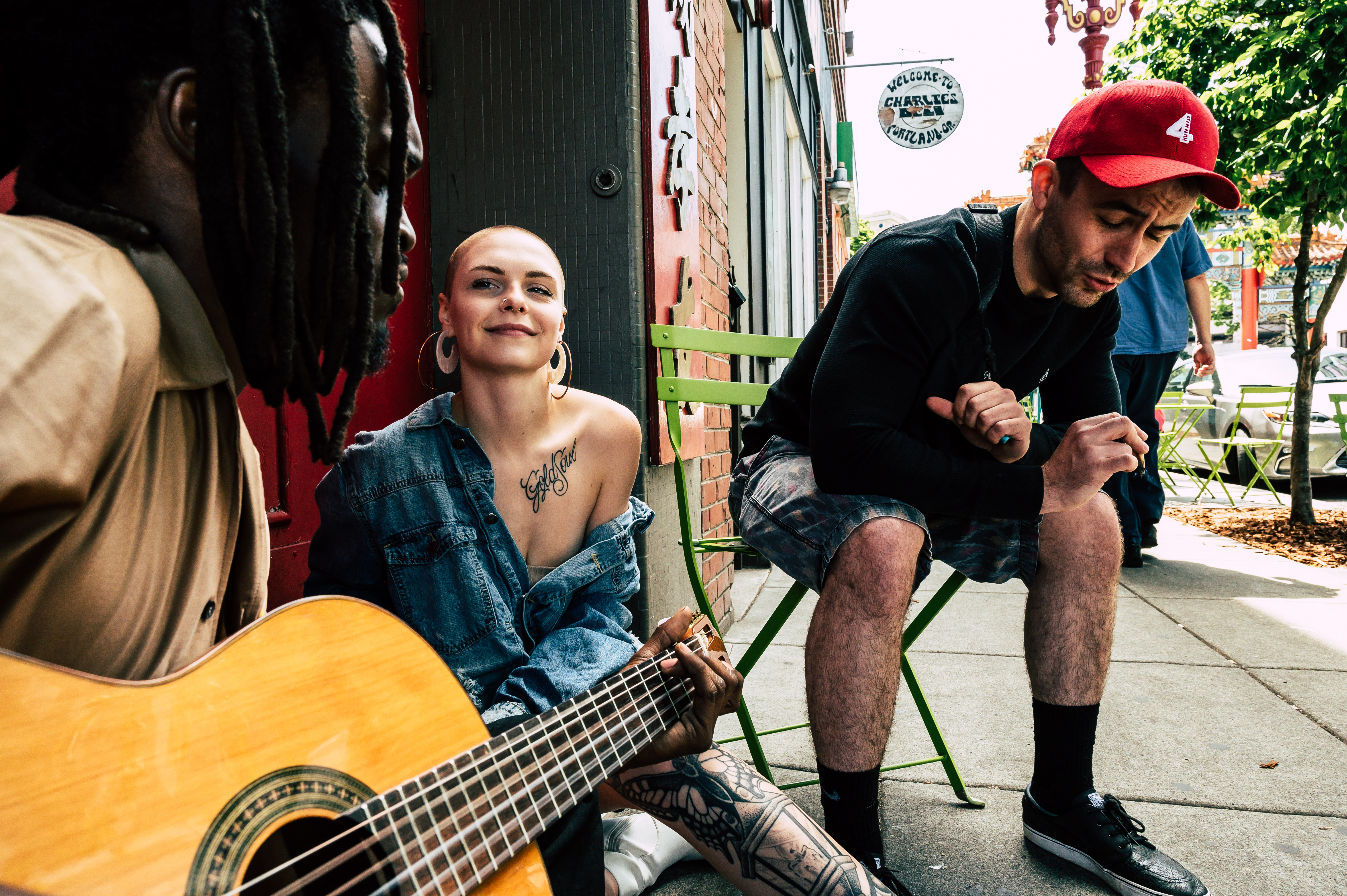 Man and Woman Sitting on Sidewalk and Playing Guitar