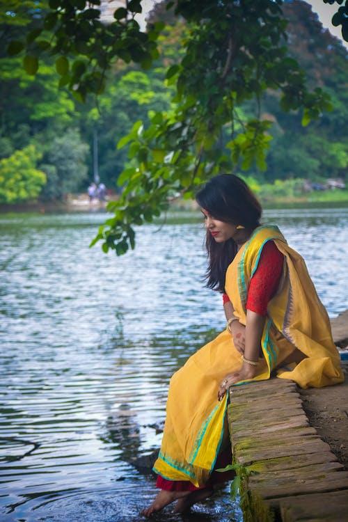 Základová fotografie zdarma na téma bangladéšská žena, krásná holka, zelený strom, žena na sobě žluté sárí
