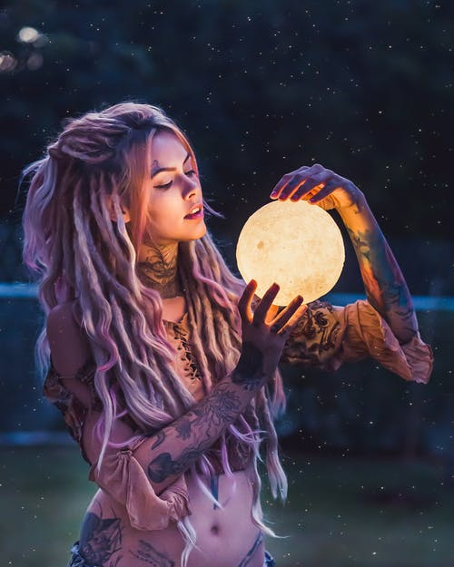 Woman With Tattoo Holding Glass Globe