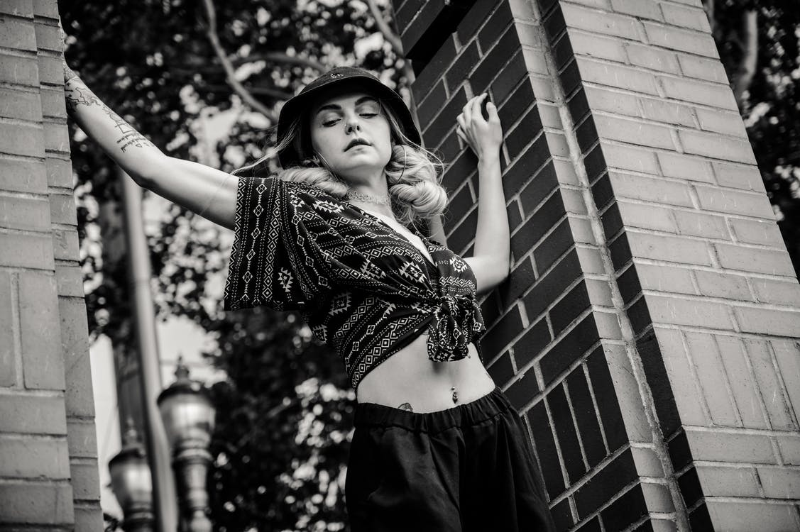 Grayscale Photo Of Woman Standing Between Brick Pillars