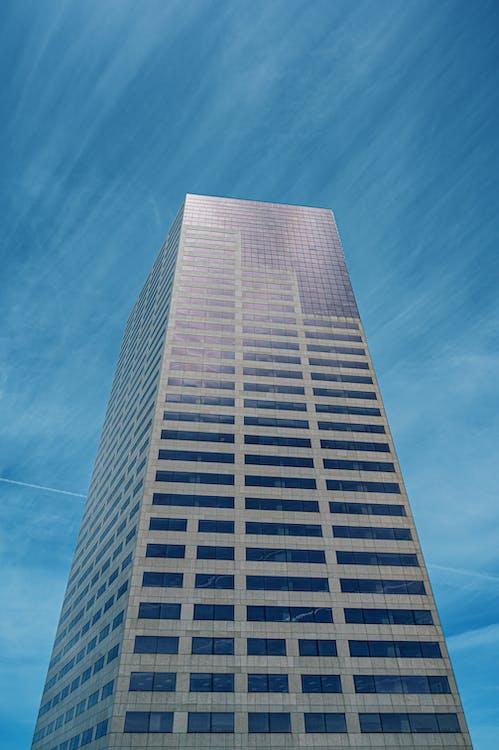 Низкоугольная фотография высотного дома под голубым небом