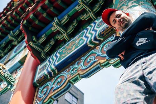 Низкоугловое фото человека, опирающегося на красный китайский столб, позирующего со скрещенными руками и смотрящего вниз
