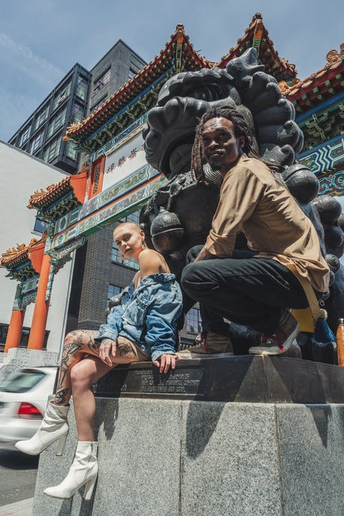 Shallow Focus Photo of Man and Woman Sitting Beside Foo Dog Statue