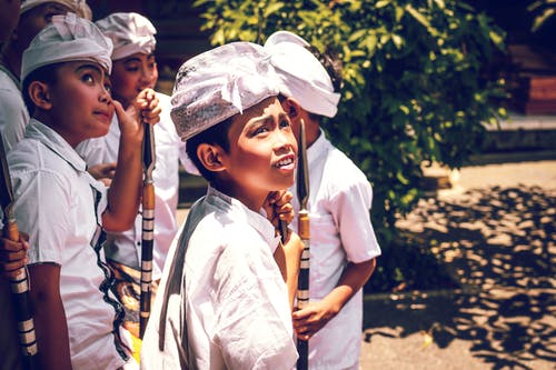 Four Boys Wearing White Hats Holding Spears