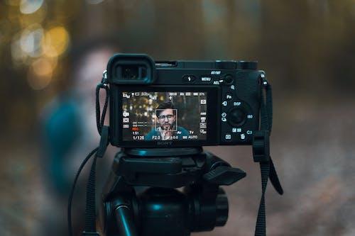 Black Dslr Camera Displaying Man in Blue Shirt