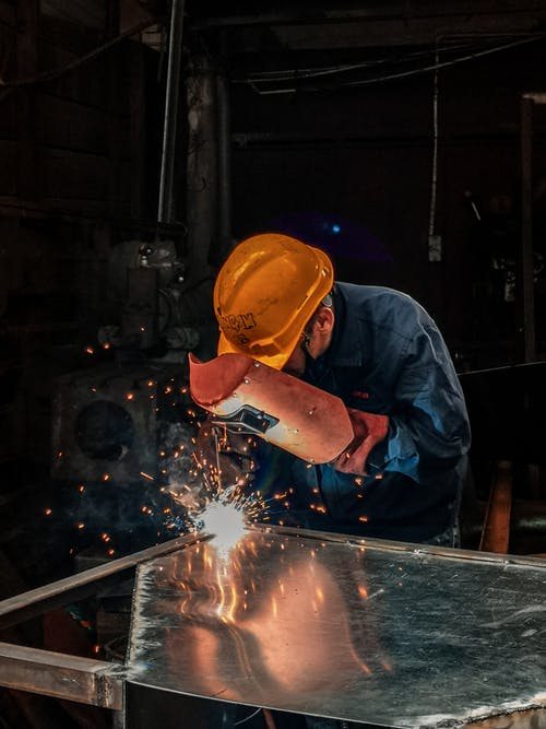 Man Welding on Gray Metal Sheet