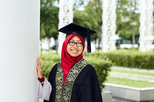 Photo of a Woman Wearing Graduation Gown and Mortar Board
