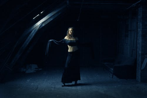 Photo of Woman in Black Outfit Standing in Dark Abandoned Building Posing While Looking Away