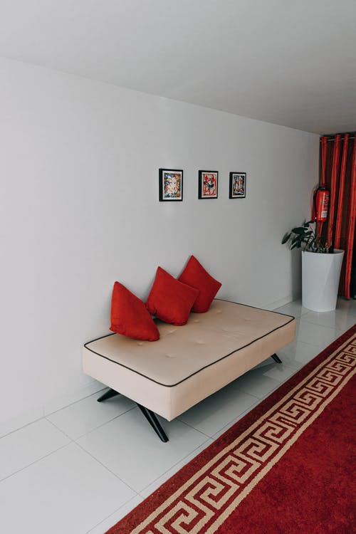 Three Red Throw Pillows on White Sofa in Room