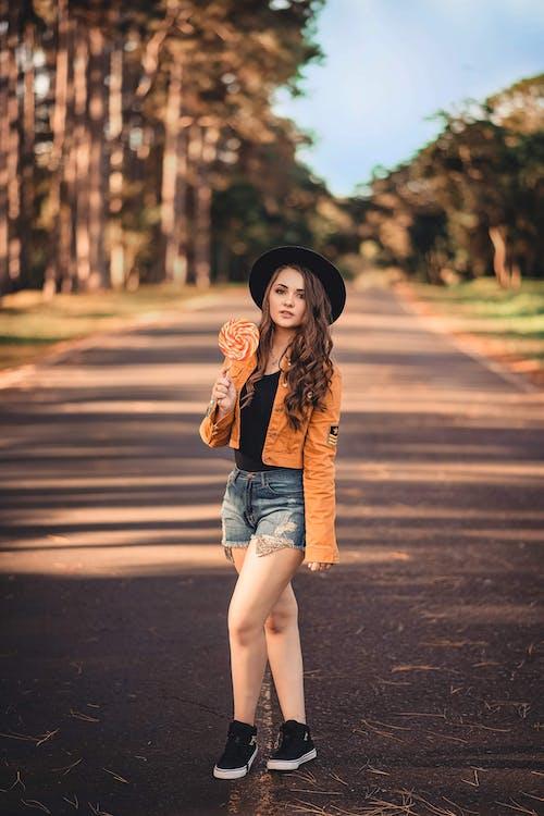 Foto profissional grátis de bonita, chapéu fedora, de pé, estrada
