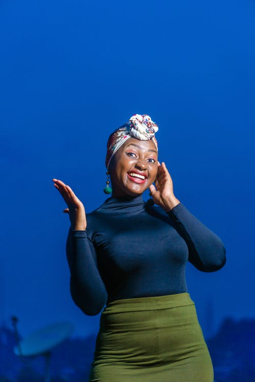 Photo of Smiling Woman in Blue Long-sleeved Fitted Top and Green Skirt Posing Against Blue Background