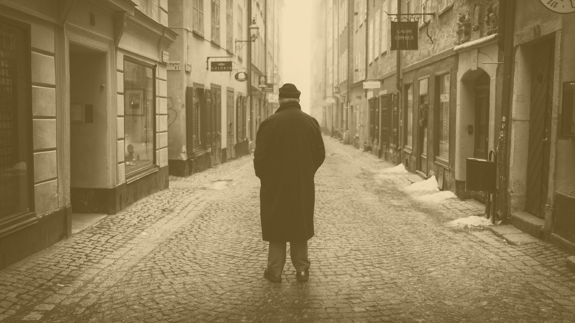 Rear View of a Man Walking on Cobblestone