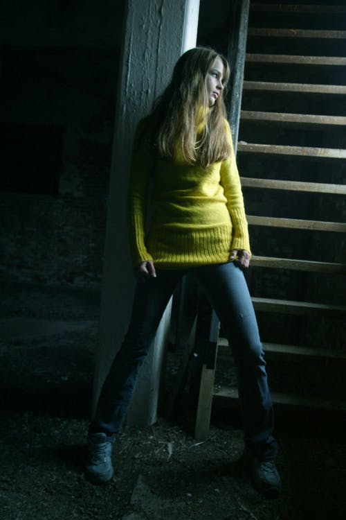 Woman Wearing Yellow Sweater Leaning on Wall