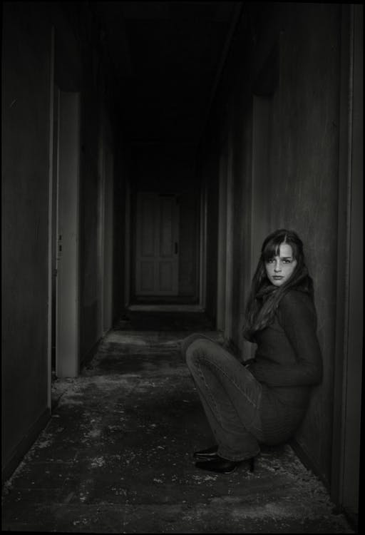 Grayscale Photo of Woman Sitting in Empty Hallway Leaning on Wall