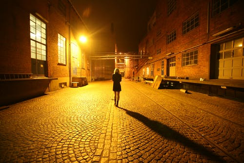 Back View Photo of Woman Walking Alone in the Middle of a Cobblestone Alley at Night