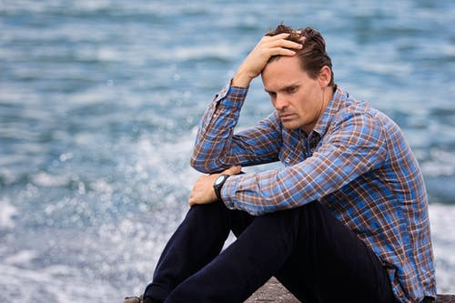Photo of a man sitting near a body of water holding his head
