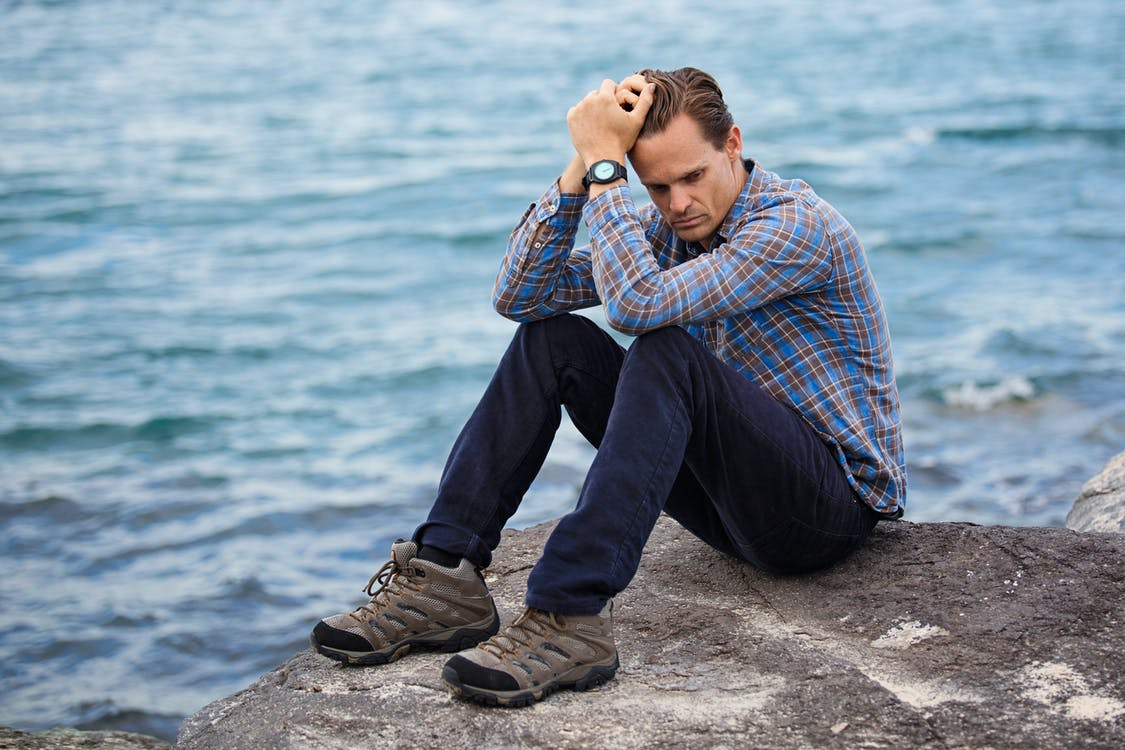 Man wearing blue and maroon plaid shirt sitting on a rock near a body of water