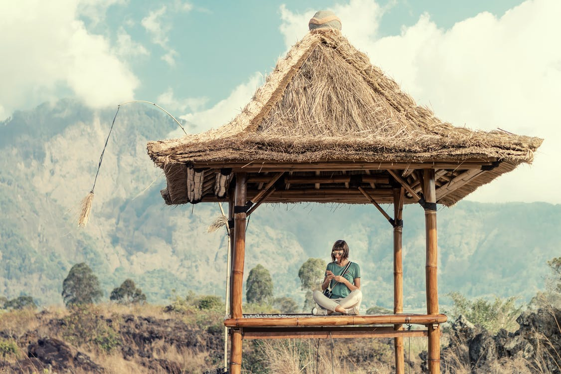 Photo of a Woman Sitting under a Thatch Roof  Gazebo