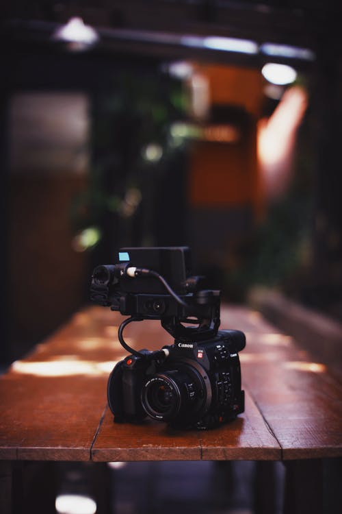 Black Dslr Camera on Wooden Table