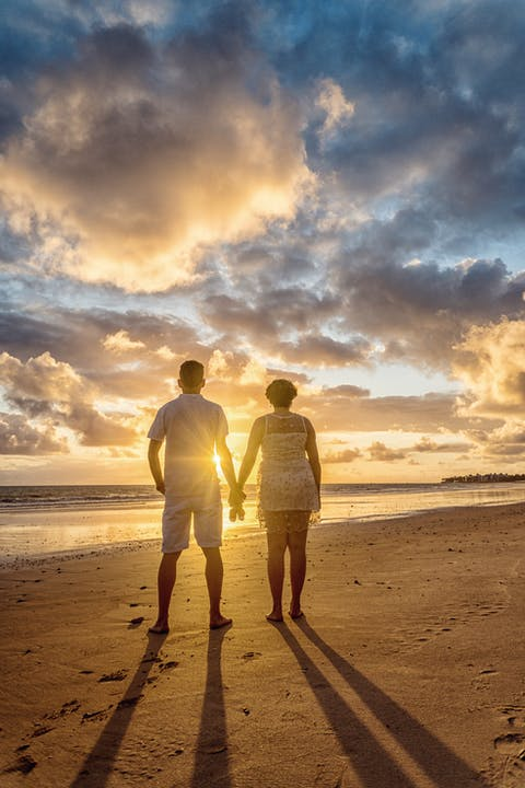 Back View Photo of Couple Standing on the Beach Looking at the Horizon