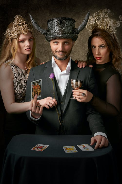 Man Wearing Gray Suit Jacket Holding Tarot Card