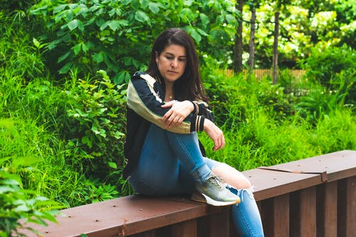 Photo of Woman Sitting Alone Brown Bench Thinking