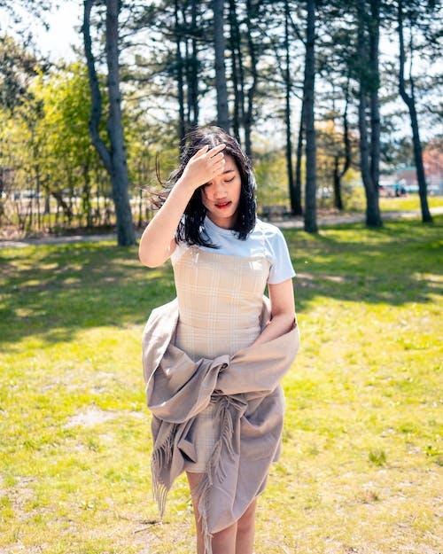 見下ろしながらポーズをとって髪に触れながら公園に立っている女性の写真
