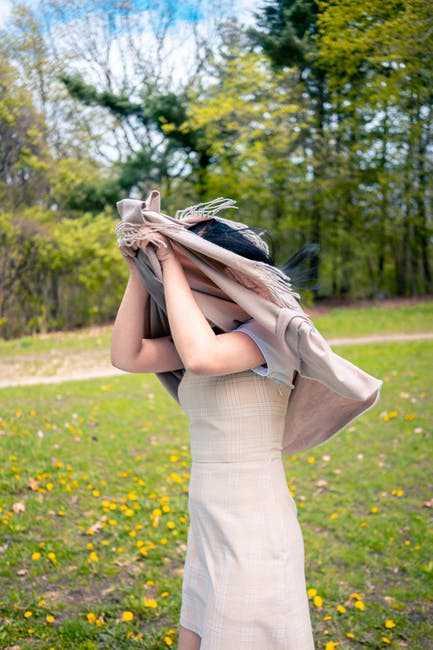 Selective focus photo of woman in dress covering a head with a gray apparel standing on green grass...