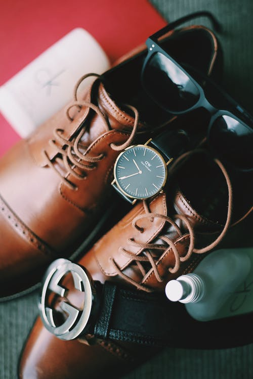 Close Up Photo of a Pair of Brown Shoes,Wrist Watch, Sunglasses,Belt and CK Spray