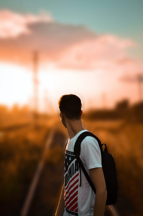 Selective Focus Photography of a Man in White Printed T-Shirt Carrying Backpack