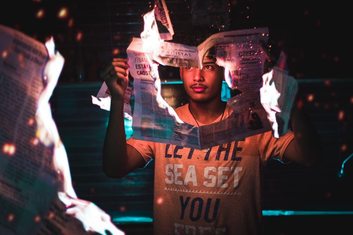 Man Holding Burning Newspaper
