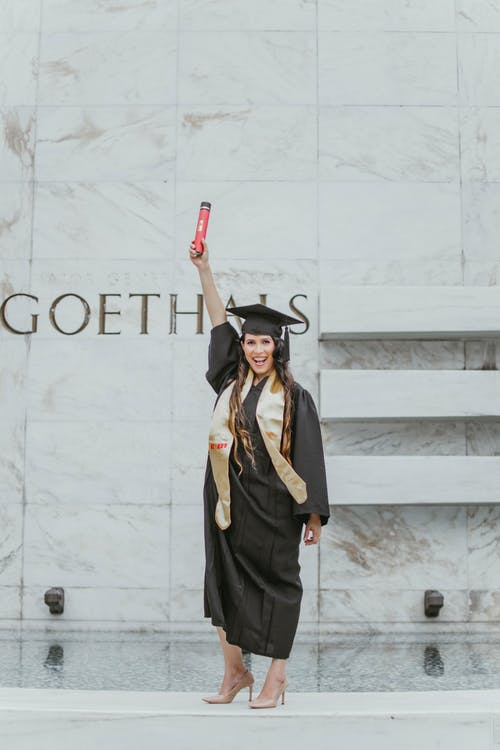 Photo of Smiling Woman in Black Academic Dress Standing In Front of Marble Wall Holding Up Diploma