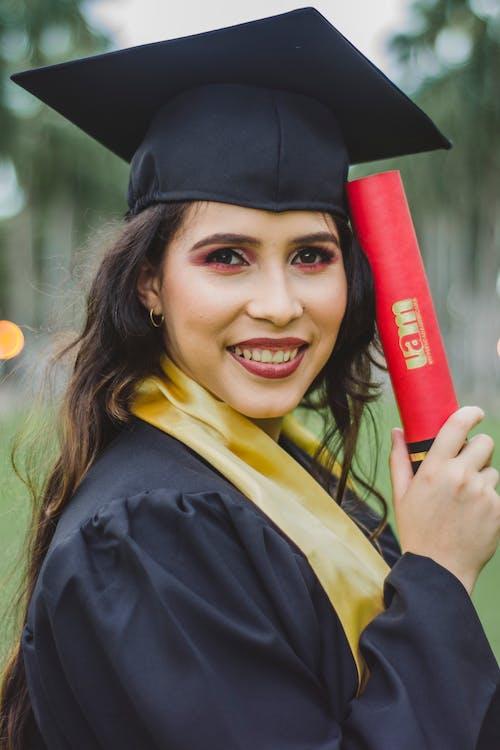Selektiver Fokus Porträtfoto Der Lächelnden Frau Im Schwarzen Akademischen Kleid, Das Diplom Aufstellung Hält