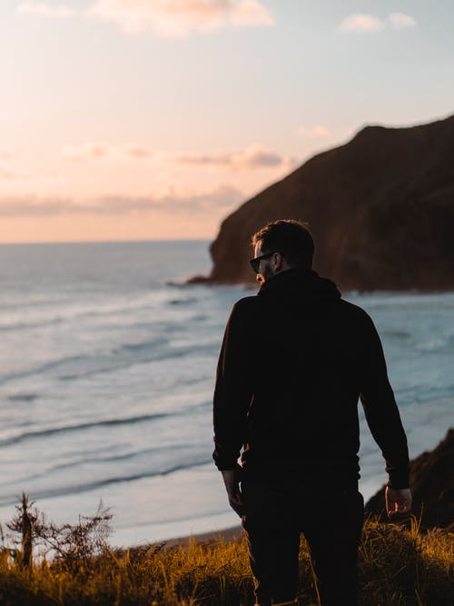 Man in Black Hoodie Standing Near Shore
