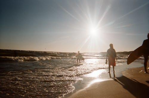 People Walking on Seashore At Dusk