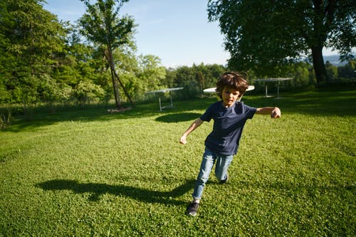 Boy Running on Green Grass