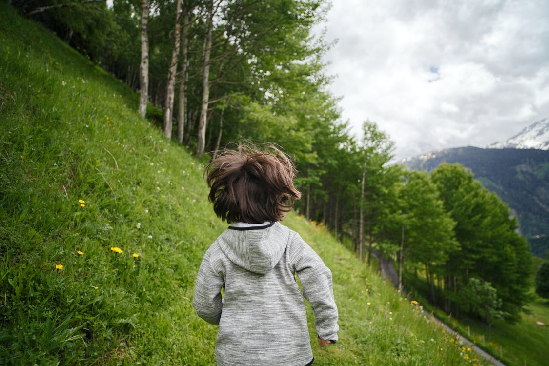 Toddler Wearing Gray Hoodie Running on Green Fields