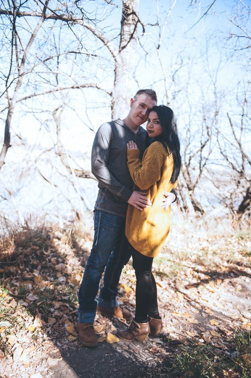 Photo of Hugging Couple Standing In Front of Bare Trees