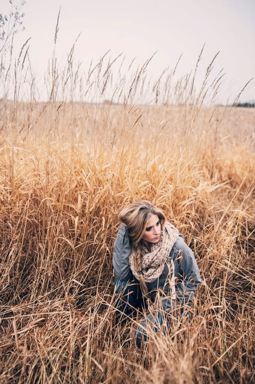 Photo of Woman Squat Posing in the Middle of Brown Grass Field Looking Away