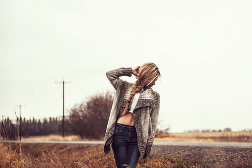 Photo of Woman in a Gray Sweater, White Tank Top, and Blue Jeans Standing on the Side of the Road Posing While Looking Away