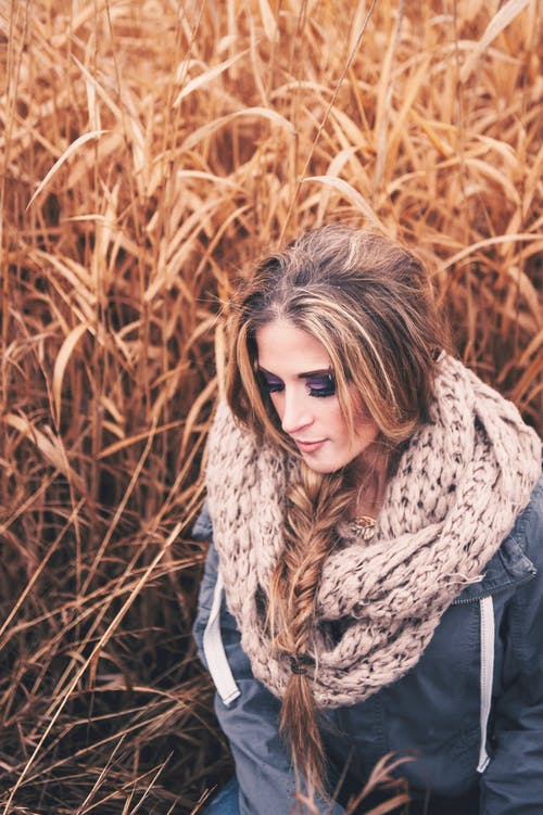 Selective Focus Photo of Woman in Blue Jacket and Knitted Scarf Posing by Tall Brown Grass