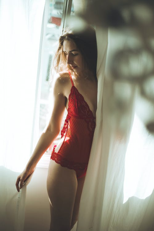Women in Red Lingerie Standing Behind White Curtain