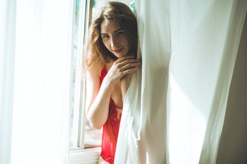 Photo of Smiling Woman in Red Lingerie Standing Behind White Window Curtain