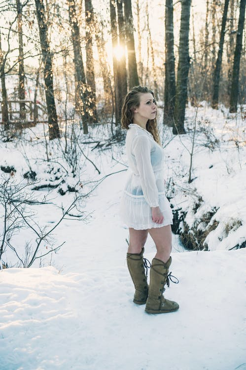 Side View Photo of Woman in White Dress and Winter Boots Standing in the Snow Near Trees