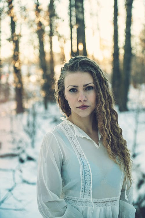Selective Focus Photo of Woman in White Dress Standing in the Snow Posing