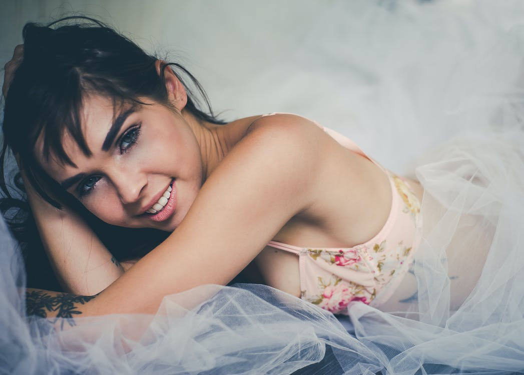 Close up Photo of Smiling Woman Wearing Pink  Floral brassiere Lying on White Sheer Cloth